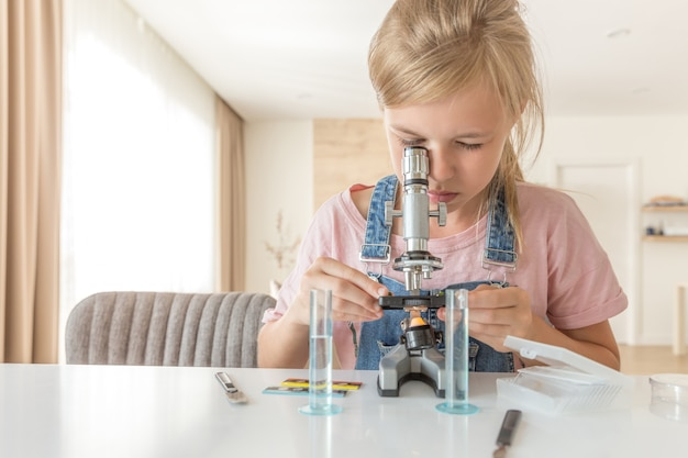 Girl with microscope at home learning chemistry and playing Premium Photo