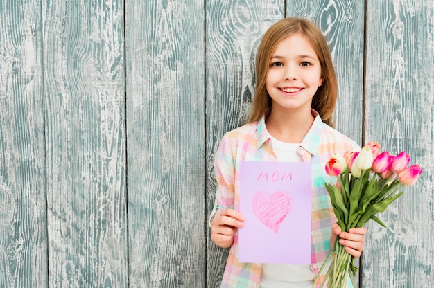 Girl with mother`s day postcard and tulips Free Photo