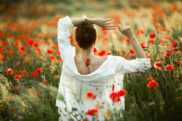 Girl with a naked back with a tattoo on it is holding hands over a head, and the beautiful poppies field Free Photo