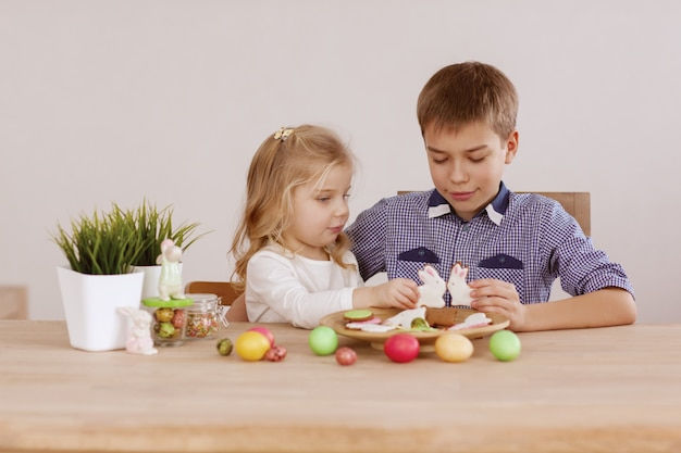 A girl with an older brother are sitting at the holiday table and laying out cookies and easter eggs Premium Photo