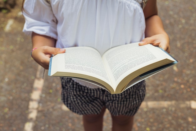 Girl with open book in shorts Free Photo