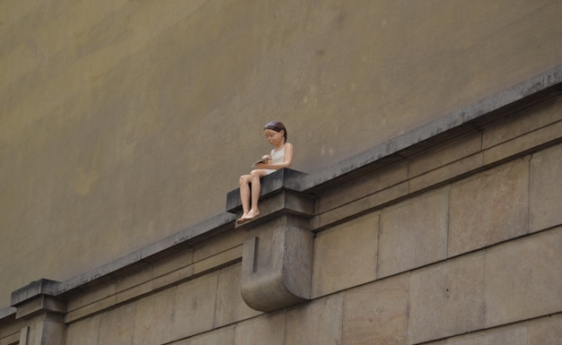 Girl with a paper plane sitting on a pedestal on a wall Premium Photo