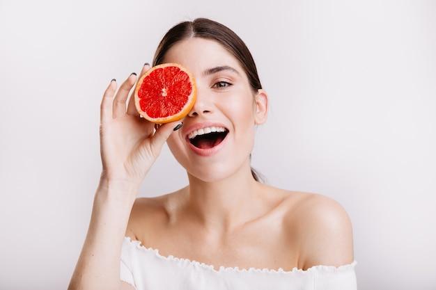 Девушка с идеальной кожей счастливо позирует на изолированной стене. портрет женской модели, поддерживающей здоровое питание. Бесплатные Фотографии