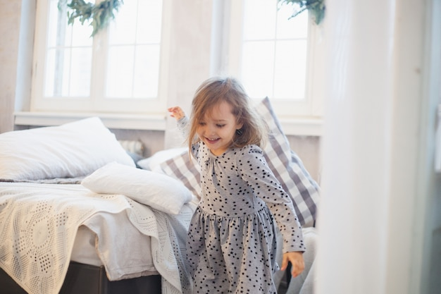 Girl with a pillow, children fight pillows on the bed, the window decorated with a christmas wreath, life, childhood Premium Photo