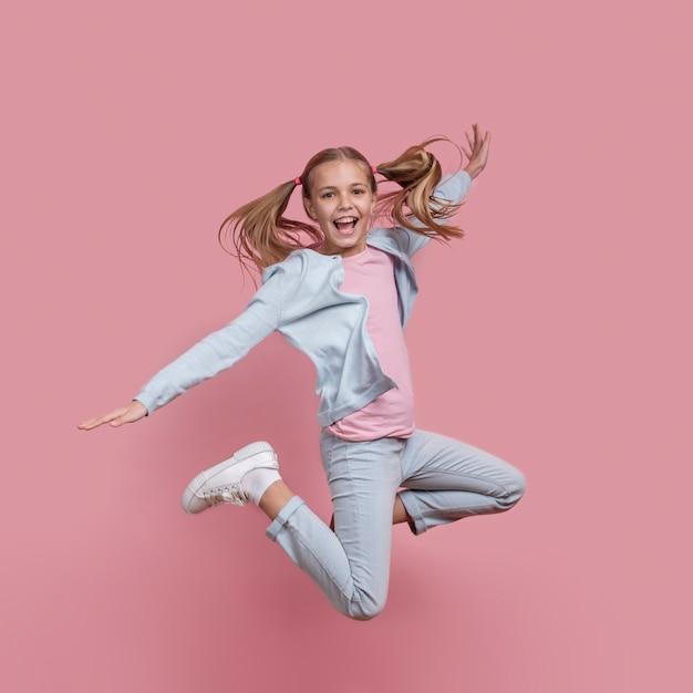 Девушка с хвостиками прыгает и улыбается Premium Фотографии