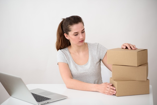 ポニーテールの少女、灰色のtシャツはラップトップに座って、段ボール箱の山を見ています。オンライン配送サービス Premium写真