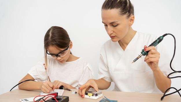 科学実験をしている保護メガネと女教師を持つ少女 無料写真