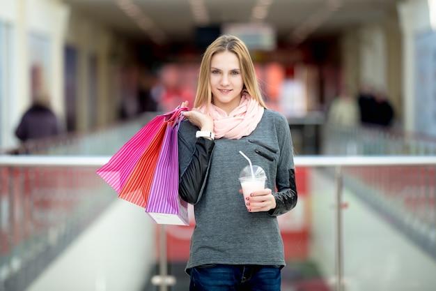 دختر با کیسه های خرید در یک مرکز خرید