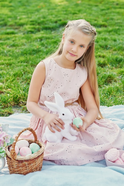 Girl with rabbit and eggs for easter in the park on green grass Premium Photo