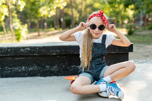 Girl with red headband sitting on skateboard Free Photo