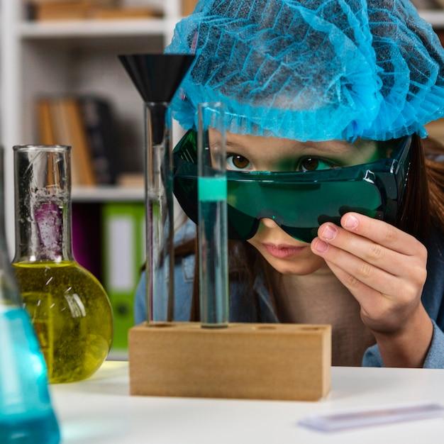 과학 실험을하는 안전 안경과 머리카락을 가진 소녀 프리미엄 사진