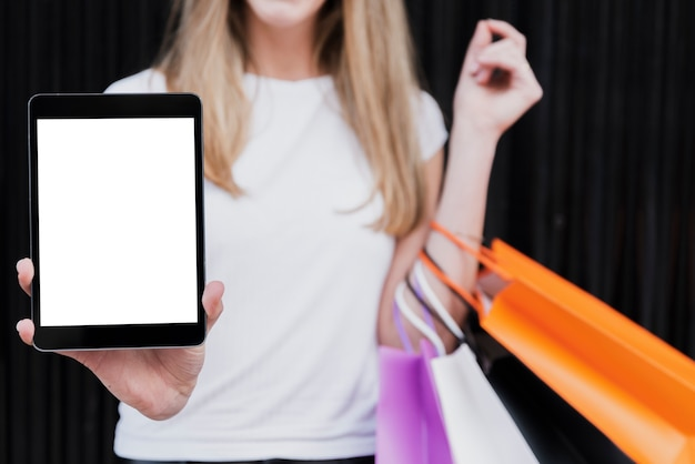 Girl with shopping bags holding tablet mock-up Free Photo