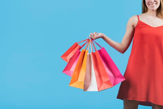 Girl with shopping bags on plain background Free Photo