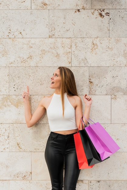 Girl with shopping bags standing by wall Free Photo