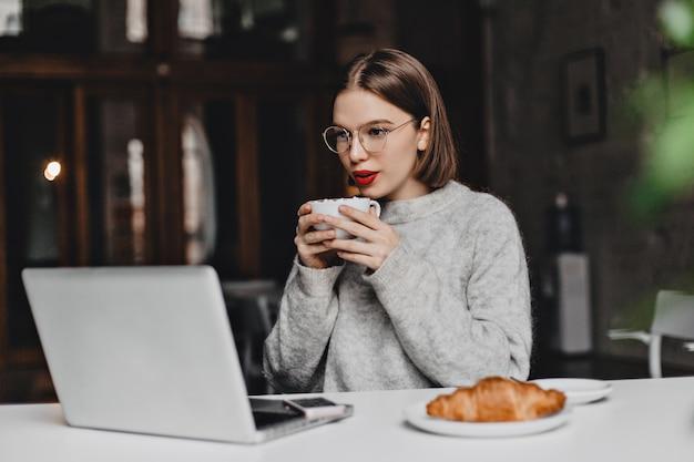 灰色のセーターを着たストレートの短い髪の少女はお茶を飲み、ノートパソコンの画面を見ます。皿の上にクロワッサンとテーブルに座って眼鏡をかけている赤い口紅を持つ女性の写真。 無料写真