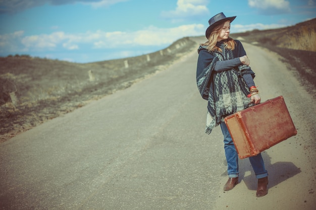 Girl with a suitcase on the road Premium Photo