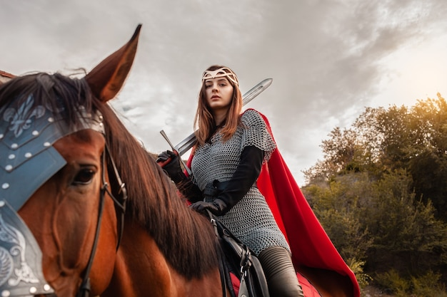 A girl with a sword on horseback against the sky. a beautiful woman in the costume of the warrior Premium Photo