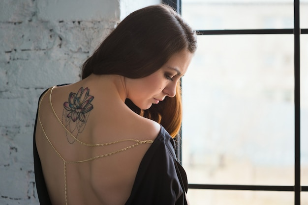 Girl with tattoo lotus on her back sad at the window Premium Photo