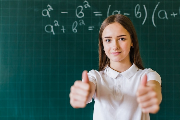 Девушка с пальцами вверх в классе математики Premium Фотографии
