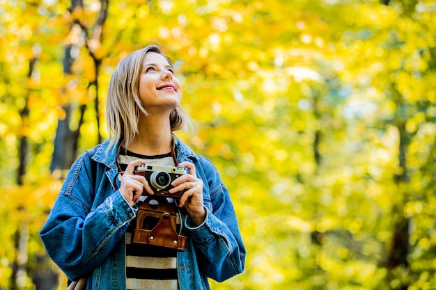 Girl with vintage camera have rest in the park in autumn season time Premium Photo