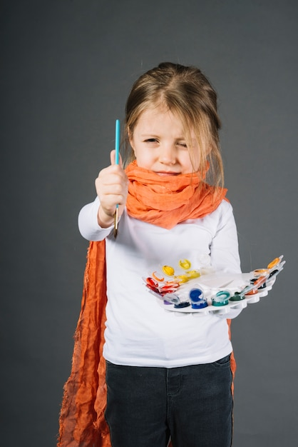 Girl with water colors and brush in hands Free Photo