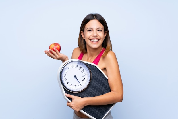 Girl with weighing machine over isolated blue  with weighing machine and with an apple Premium Photo