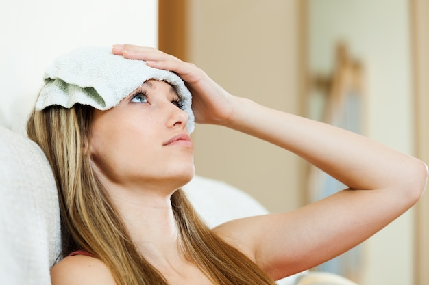 Girl with wet towel on forehead Free Photo