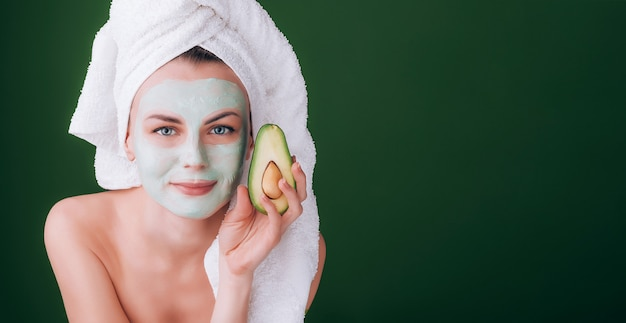 Girl with a white towel on her head with a nutritious green mask on her face and an avocado in her hands on a green background with space for text Premium Photo