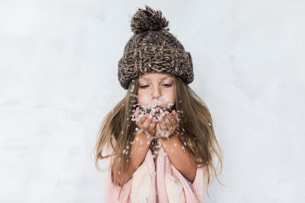 Girl with winter hat blowing snow Free Photo