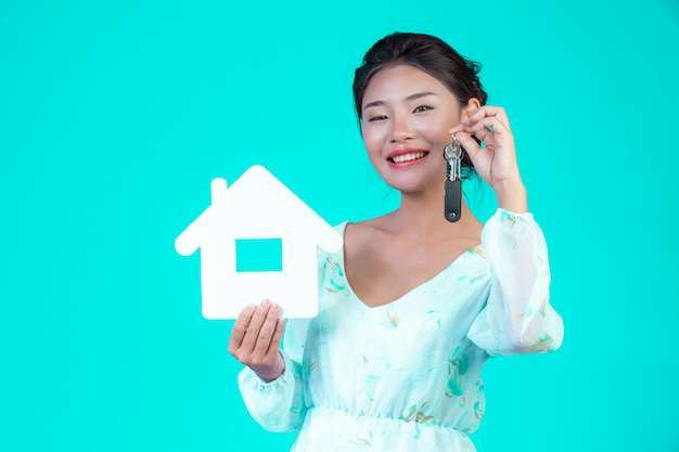 The girl wore a white long-sleeved shirt with floral pattern, holding the house symbol and holding a key ring with a blue . Free Photo