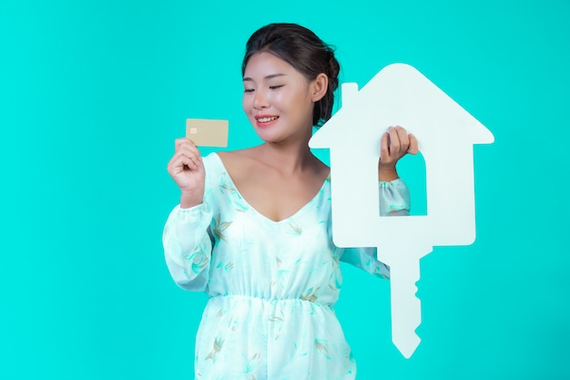 The girl wore a white long-sleeved shirt with floral pattern, holding a white house symbol and a gold credit card with a blue . Free Photo