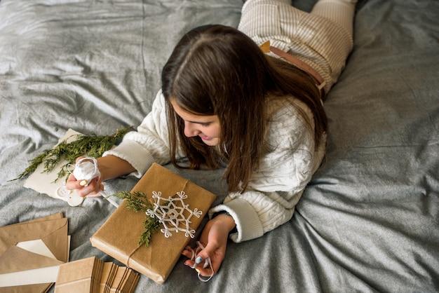 クリスマスの装飾で贈り物を包む女の子 Premium写真