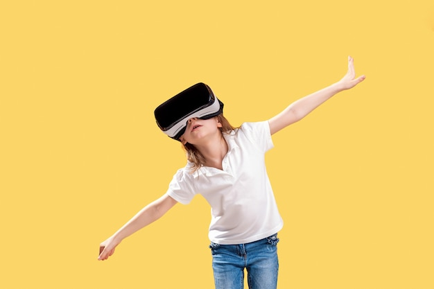 Girl  y.o in formal outfit wearing vr glasses putting hands out in excitement isolated on yellow . child using a gaming gadget for virtual reality. virtual technology Premium Photo