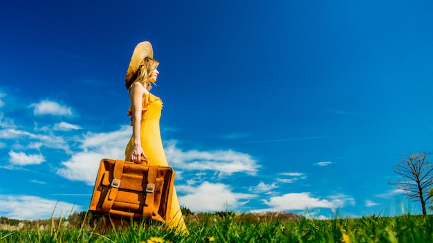 Girl in yellow dress and suitcase on mountain meadow with dandelions Premium Photo
