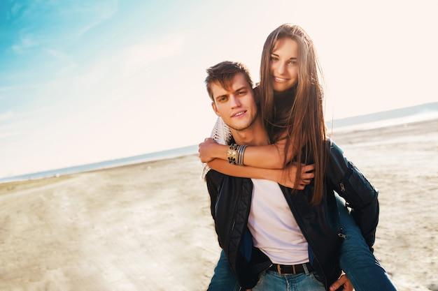 Подруга и парень обнимаются счастливы. молодая милая пара в влюбленности датируя на солнечной весне вдоль пляжа. теплые цвета. Бесплатные Фотографии