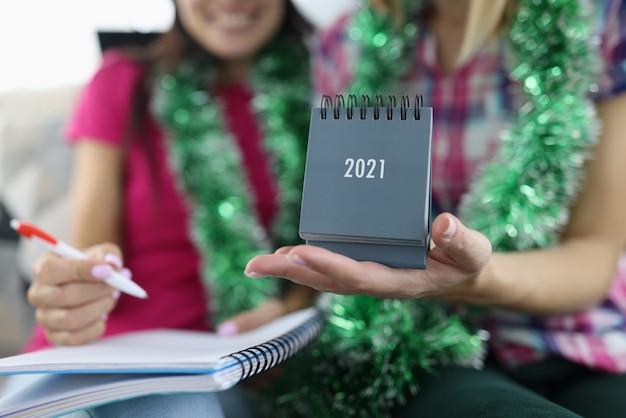 여자 친구는 달력 2021을 그녀의 손에 잡고 있습니다. 프리미엄 사진