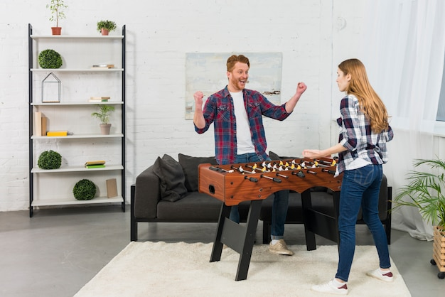 Girlfriend shrugging in front of man celebrating his success near the table soccer at home Free Photo