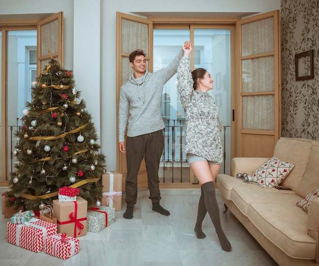 Girlfriend spinning dancing with boyfriend near christmas tree Free Photo