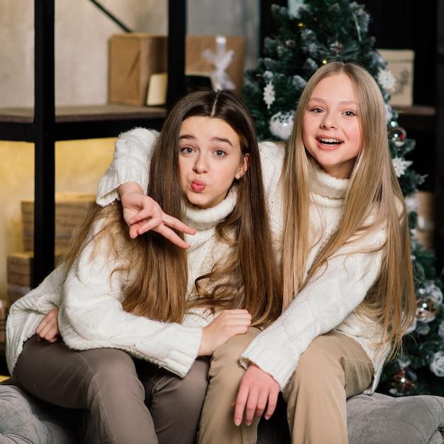 大晦日とクリスマスを祝い、ベッドでみかんを食べるガールフレンド。贈り物や金色のボールで飾られたモミの枝があります。 Premium写真