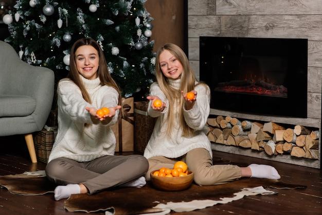 Подруги празднуют канун нового года и рождества и едят мандарины на кровати. есть подарки и украшенные золотыми шарами еловые ветки. Premium Фотографии