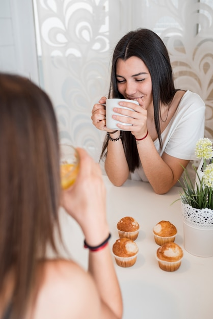 Girlfriends drinking tea at home Free Photo