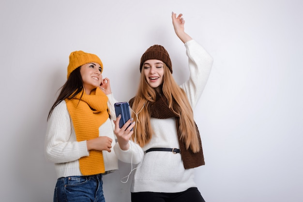 Girlfriends in hats and scarves listen to music Premium Photo