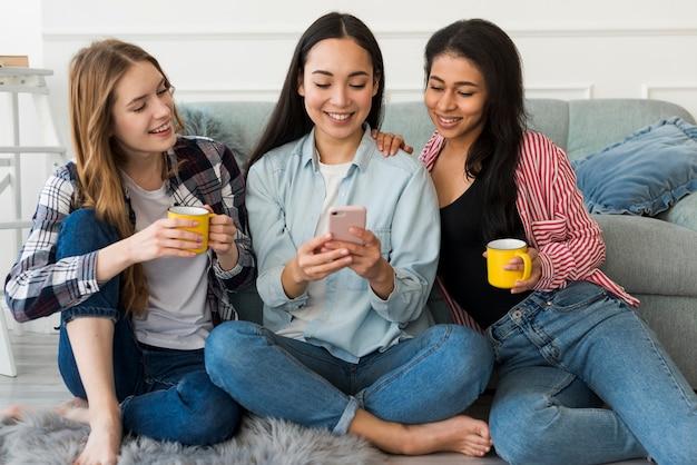 Girlfriends sitting on floor looking at smartphone Free Photo