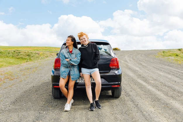Girlfriends standing near car on road Free Photo