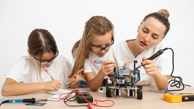 로봇 자동차와 함께 과학 실험을하는 소녀와 여성 교사 무료 사진