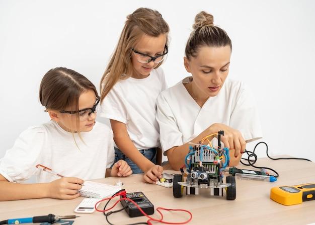 과학 실험을 함께하는 소녀와 여성 교사 무료 사진