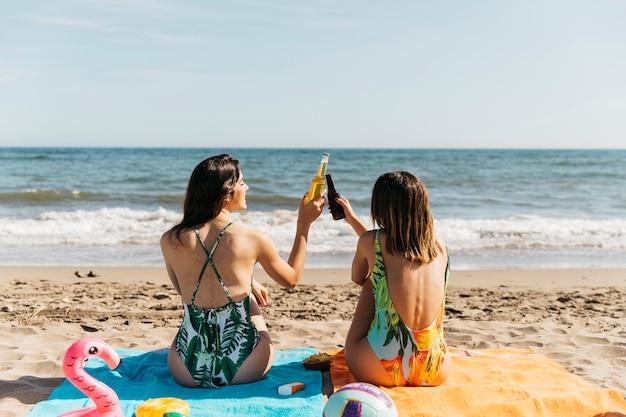 Девушки на пляже тосты с пивом Бесплатные Фотографии