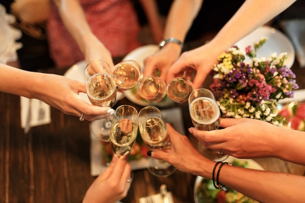 Girls cheers glasses with champagne in restaurante Premium Photo