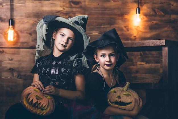 Девушки одевают ведьм с тыквами и угощениями на хэллоуин на деревянных декорациях Premium Фотографии