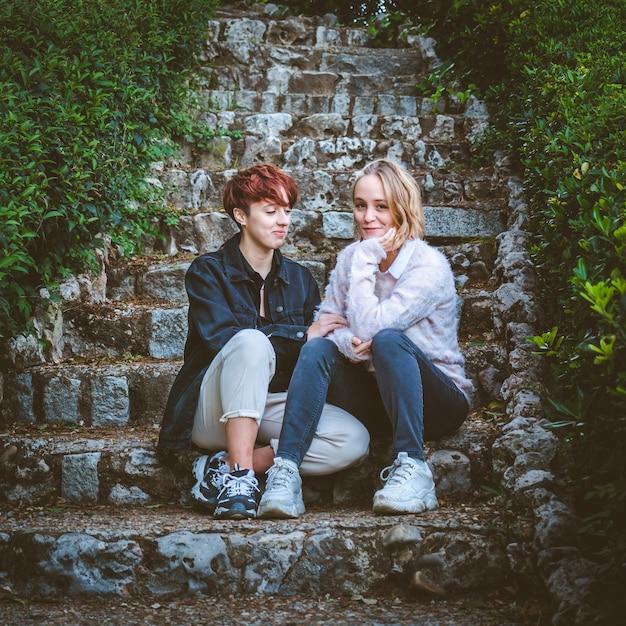 公園の石の階段でリラックスするのが大好きな女の子のカップル Premium写真